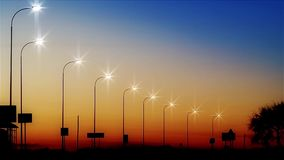 Street lights along the road turning on against twilight background stock footage