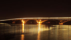Street lights on bridge reflected in river at night Stock Image