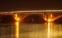Street lights on bridge reflected in river at night Stock Images