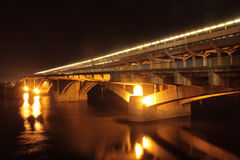Street lights on bridge reflected in river at night Royalty Free Stock Images