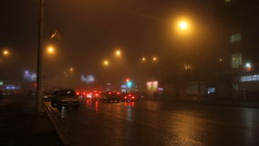 Street lights of city in fog and cars on road. stock footage