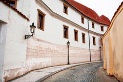 Street lights on a curved road with old cobblestones and white houses Royalty Free Stock Photography