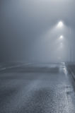 Street lights, foggy misty night, lamp post lanterns, deserted road in mist fog, wet asphalt tarmac, car headlights approaching. Blue key, vertical scene Stock Images