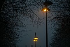 Street lights in foggy weather, late autumn, mistic haze or mist.  Royalty Free Stock Photography