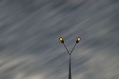 Street lights over motion blur sky Stock Photos