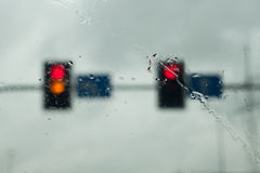 Street lights on a rainy day. Street lights seen from an inside of a car through a windshield on a rainy day Royalty Free Stock Photo