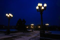 Street lights and road illuminated street lamps and snowing in winter at twilight. Vintage lamp post, walkway Royalty Free Stock Photo