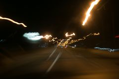 Street lights in speeding car in night time, light motion with slow speed shutter view from inside front of car.  Stock Image