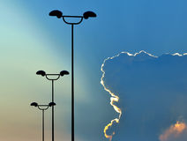 Street lights at sunset. Sun behind the clouds and street lights Stock Image