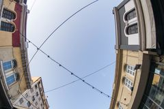 Street lights between two buildings. A picture of small street lights in wires hanging between two buildings with windows,in  a town in  Greece,Thessaloniki Stock Photography