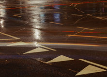Street lines. Wet street with traffic stripes and lines and lights from passing traffic Royalty Free Stock Images