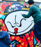 Street Lisbon graffiti. LISBON, PORTUGAL - DECEMBER 23, 2014: Boys painting graffiti on the wall in Lisbon.Along with London, Berlin, New York and others, Lisbon Stock Photo