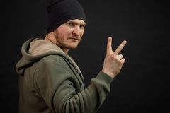Street man in sporty clothes showing two fingers. Victory gesture. peace simbol Royalty Free Stock Images