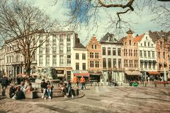 Street with many people relaxing outdoor, at square with cafe and old buildings of historical city. BRUSSELS, BELGIUM - APR 2: Street with many people relaxing Royalty Free Stock Photo