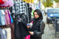 Street market. Girl buys clothes in a street market Royalty Free Stock Images