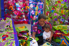 Street market in Mexico. A mother holds a child amid colourful clothing for sale in the Easter week San Cristóbal de las Casas, Chiapas, Mexico Royalty Free Stock Image