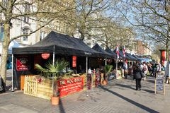 Street market, Piccadilly Gardens, Manchester. Looking along a row of covered stalls at an open air street market in Piccadilly Gardens, Manchester, England. A royalty free stock images