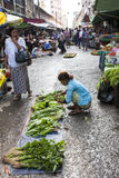Street Market in Yangon. A vendor sells green lettuces at a street vegetable market in downtown Yangon, Myanmar Royalty Free Stock Photo