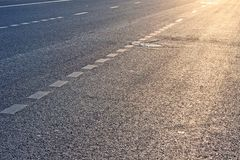 Street marking. Abstract background representing the street / road marking and asphalt texture / pattern on the urban street during sunrise / sunset. Portrait Royalty Free Stock Photography