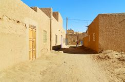 On the street in Merzouga village, Morocco. Merzouga, Morocco - Jan 6, 2017: On the street in Merzouga village. Two Moroccan men in white djellaba talk on the Stock Image