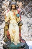 On the street and among a mesh fence the almighty son of God. Sculpture of wood of Jesus Christ, son of god sitting on the throne Royalty Free Stock Images