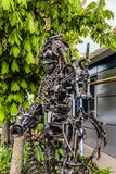 Street metal sculpture of a robot with machine gun made of old cars parts and details, auto-waste. Stock Image
