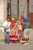 Street models in Havana, Cuba getting a tourist family to take a picture with them in colourful traditional dress. This is common in the caribbean island country stock images