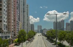 The street of the megalopolis, buildings, lampposts, the road with cars, trees along the road against the b. The street of the modern city with high-rise houses stock images