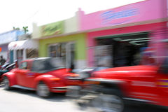 Street Movements. Slow exposure blurs the vehicles and store fronts in this picture as I shot from the inside of a moving vehicle Royalty Free Stock Photos