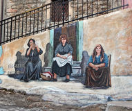 Street Mural in Orgosolo. Mural of three women sitting outdoor  by the artist  Pasqualino Baingiu in Orgosolo,Sardinia Stock Images