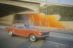 Street mural under an overpass with a red mustang driving past Royalty Free Stock Images