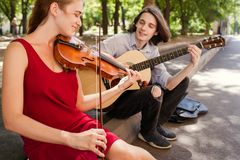 Street music duo performance romance freedom. Street music duo group performing in a park. free spirits hippie romance concept Royalty Free Stock Photography