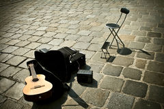 Street music - guitar, chiar and pavement Stock Image