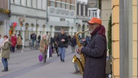 Street music instrumentalist black old man playing on saxophone for passersby people at city in unfocused in slow motion stock footage