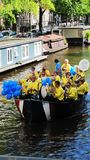 Street music players. Street musicians in yellow T-shirts play music on a boat through Amsterdam canals royalty free stock photo