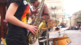 Street music saxophone. Street musicians gave live concert with a saxophones on the street