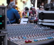 Street music show. Interesting perspective of a street music performance.Selective focus on the sound master command desk,the artist and the audience are out of Stock Photography