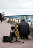 Street Musician. And entertainer squatting down beside cases, with saxaphone propped beside him, preparing to play Royalty Free Stock Photo