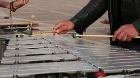 A street musician in a black T-shirt is playing a xylophone. A street musician in a black T-shirt is playing a xylophone stock video footage