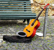Street musician on break. Guitar and a hat with coins stand on Stock Photos