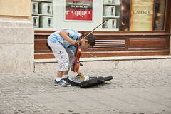Street musician in Bucharest, Romania. A little musician on the Bucharest street counting his earnings Royalty Free Stock Photography