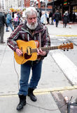 Street musician busker. Man with white hair and beard playing a guitar on a street in downtown Ottawa, Ontario Stock Photos