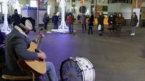 Street musician in the center of Moscow sings and plays guitar and drums. stock footage