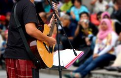 Street musician with guitar, with audience in background Stock Image