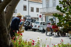 Street musician with hat plays jazz music for tourists - street scene stock photography