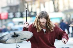 Street musician performing with drum. Man playing drums on the street. Drummer playing drums on blured city background royalty free stock images