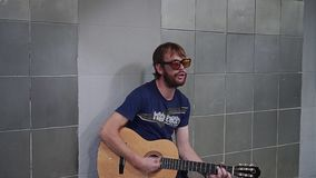 Street musician performs in the underpass. He emotionally sings a song with a guitar. Creativity. Evening atmosphere stock video