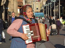 Street musician playing accordion. An old lady playing accordion on Buchanan Street in Glasgow, 2009 Stock Image