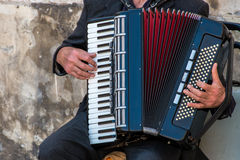 Street musician playing an accordion. For alms at sunset in Syracuse, Ortigia, Sicily, Italy Stock Image