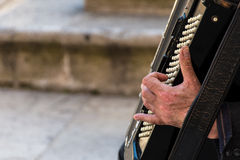 Street musician playing an accordion. For alms at sunset in Syracuse, Ortigia, Sicily, Italy Stock Photography